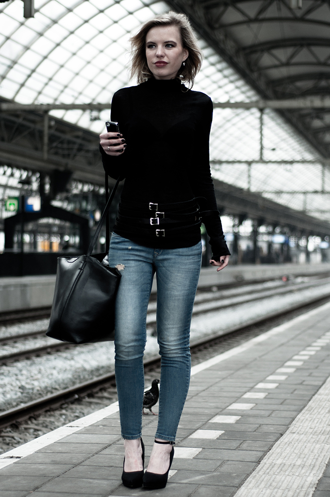 Model of duty fashion blogger black top blue jeans outfit