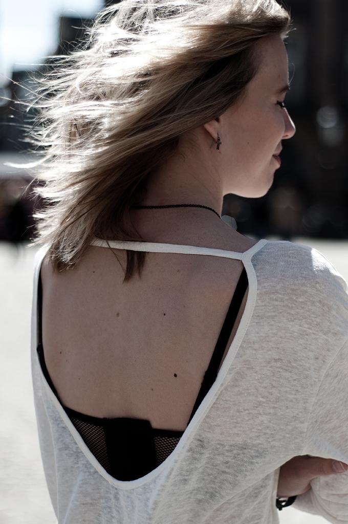 Fashion blogger blonde girl messy hair tiny cross earring mesh fishnet bra cream linen tee