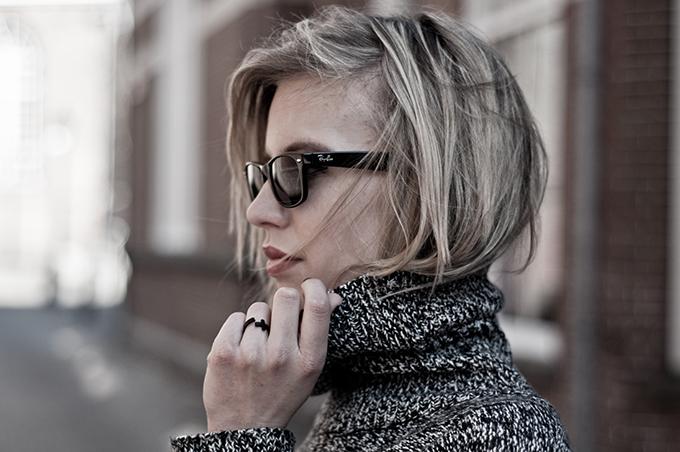 girl hair tucked in turtleneck sweater cross ring ray ban wayfarer