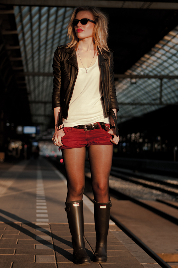 Fashion blogger wearing festival look distresses ripped oxblood shorts Hunter wellies rainboots