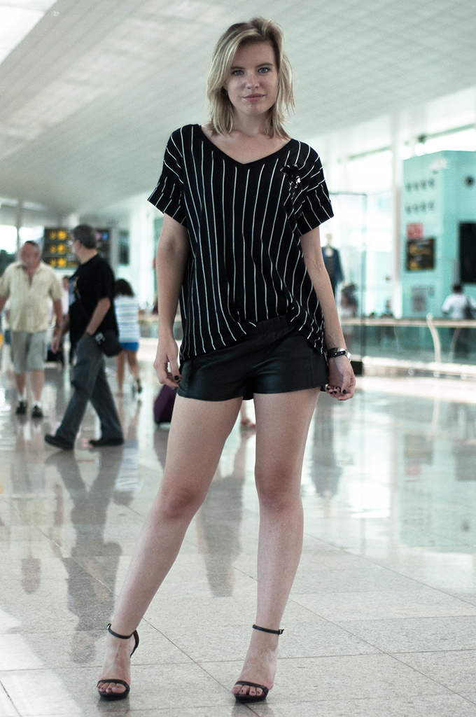 Fashion blogger wearing outfit look flying BCN airport leather shorts vintage tappered baseball tee oversized strappy zara heels