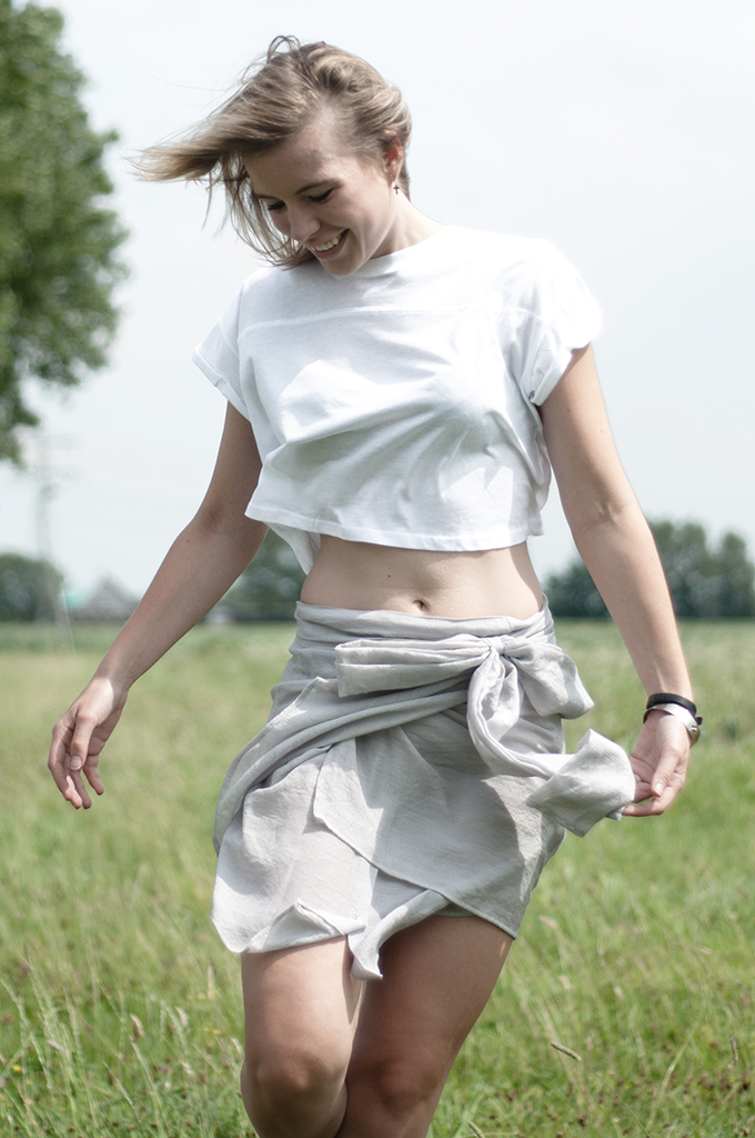Happy girl in the grass enjoying summer outfit easy breezy comfy comfortable smiling crop top shirt skirt wrap