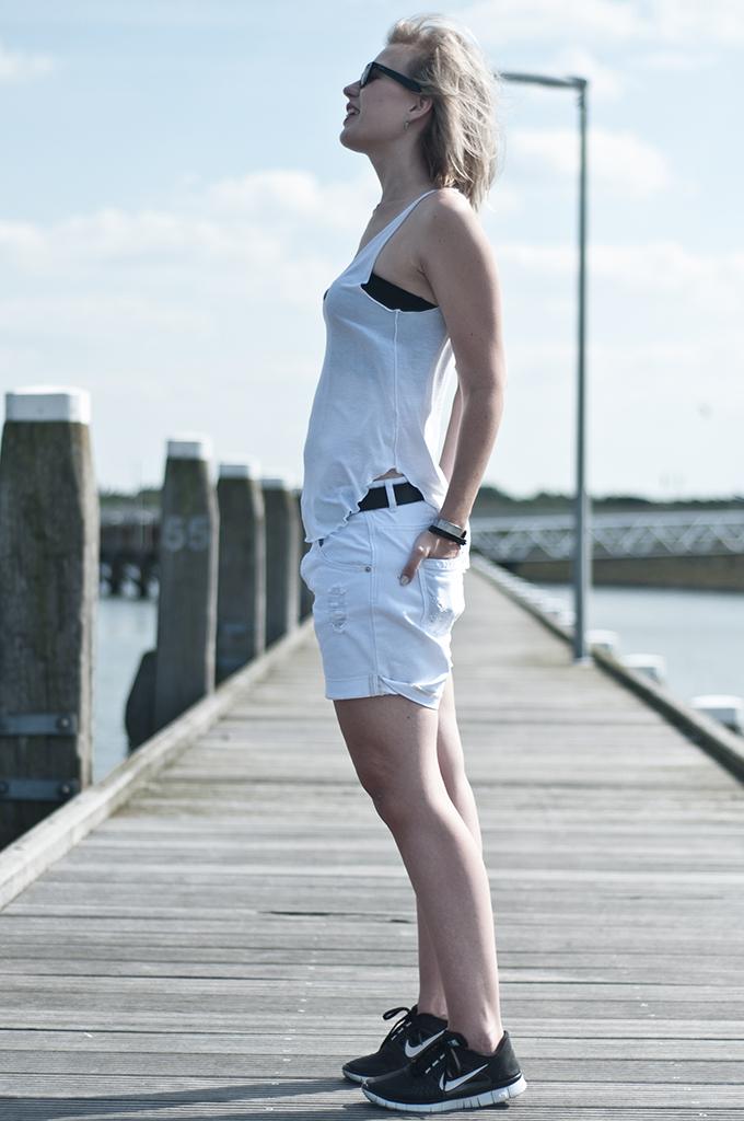Fashion blogger model oversized boyfriend shorts all white tank top bandeau crop top Nike free
