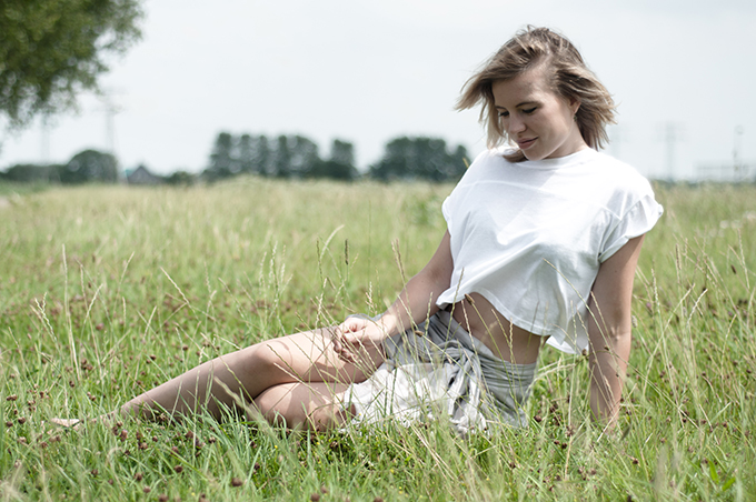 Long summer days girl model off duty in the grass editorial outfit crop top bare mid riff belly shirt skirt