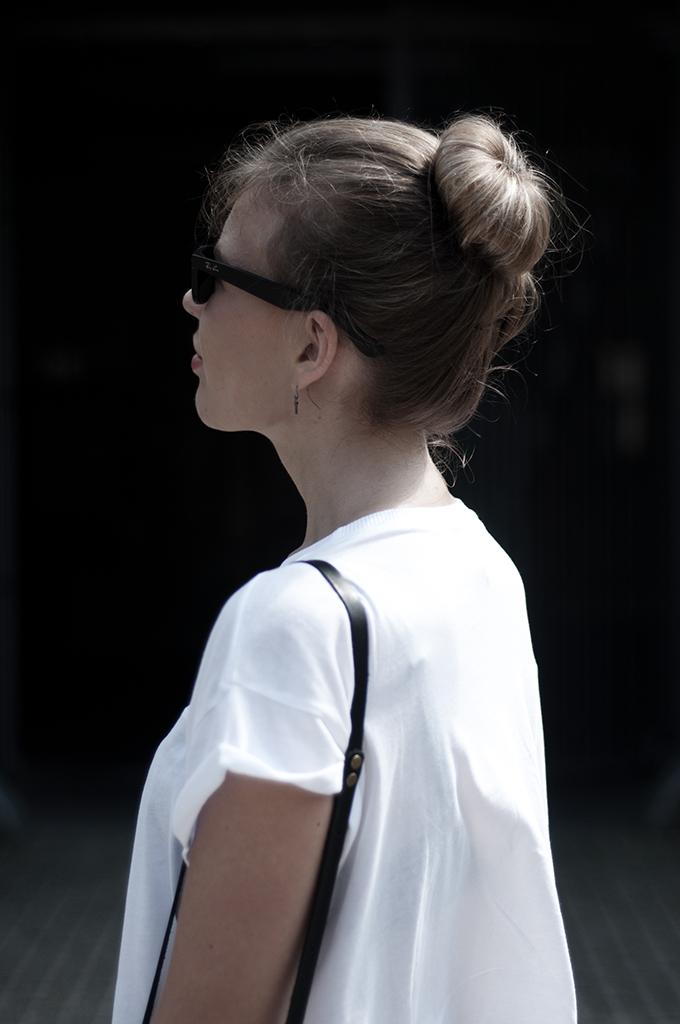 Fashion blogger wearing cross earrings hair donut bun ray ban wayfarer model off duty streetstyle