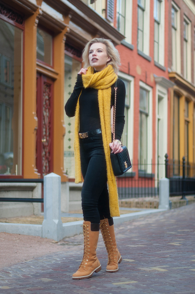 RED REIDING HOOD: Fashion blogger wearing moschino belt all black everything outfit timberland lace-up boots designer bag outfit