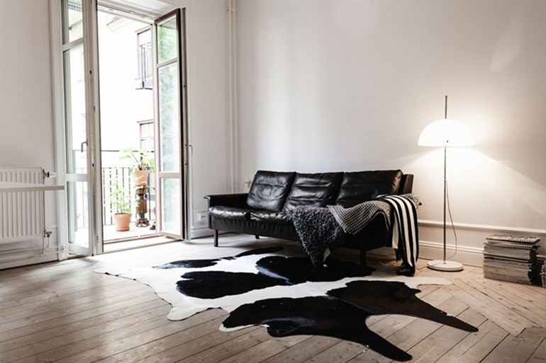 RED REIDING HOOD: Black white spotted cowhide rug minimal interior leather couch