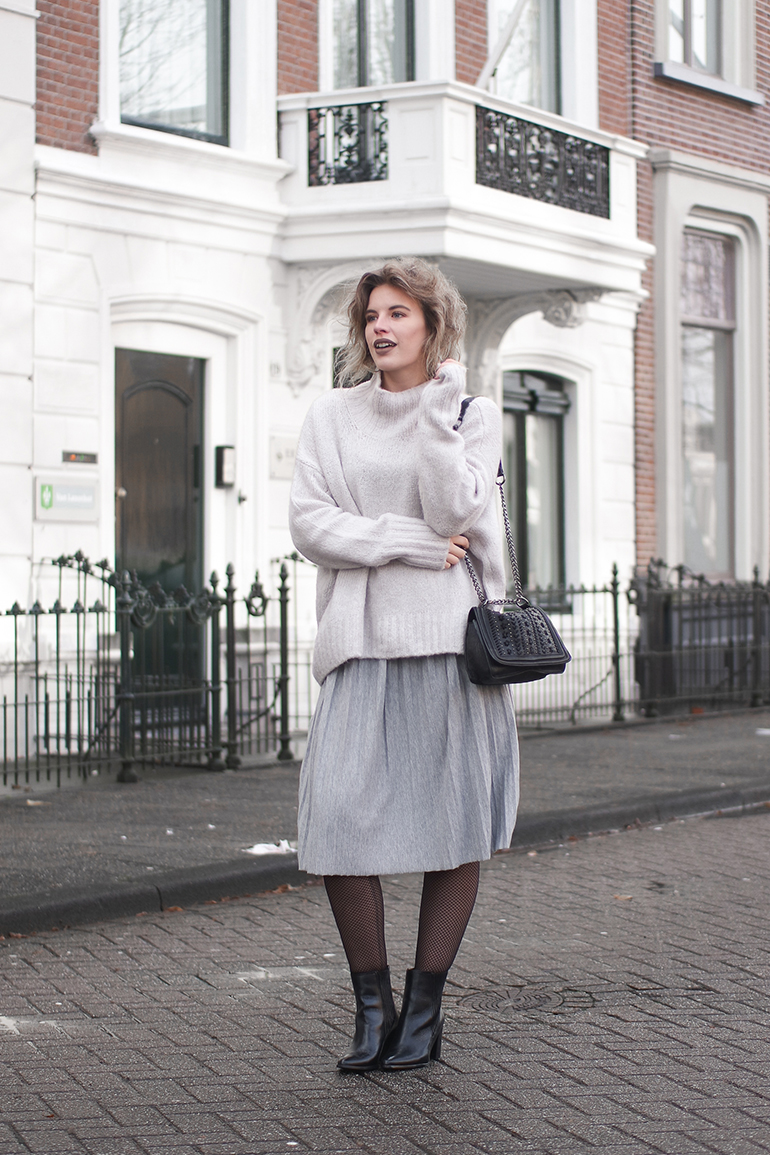 RED REIDING HOOD: Fashion blogger wearing oversized jumper pleated skirt outfit fishnet tights winter layering